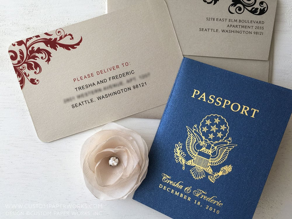 Passport wedding invitation with blue cover and tan shimmer pages inside, designed by Custom Paper Works